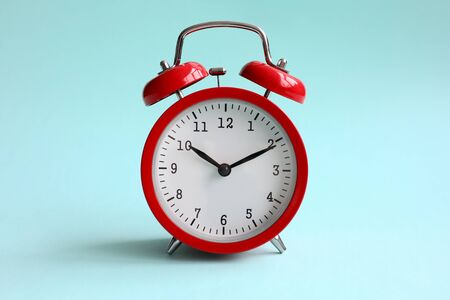 Czerwony budzik na turkusowym tle pokazuje 10 godzin 10 minut wieczorem lub rano. Koncepcja czasu do wyboru Zdjęcie Seryjne