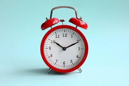 El despertador rojo sobre fondo turquesa muestra 10 horas y 10 minutos por la noche o por la mañana. Concepto de tiempo para elegir Foto de archivo
