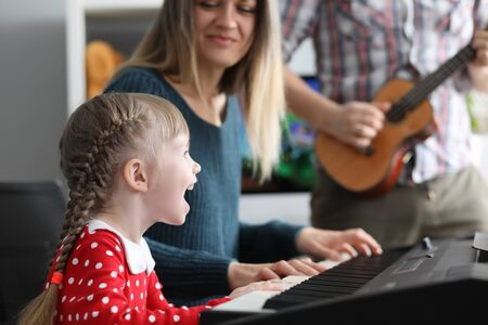 Portrait of cheerful mom looking at daughter with happiness and gladness. Father playing guitar, mother playing on synthesizer and little girl singing. Parenthood and childhood concept