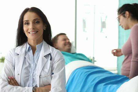 Portrait of beautiful lady looking at camera with happiness. Wife speaking with ill husband about diagnosis on background. Healthcare and treatments concept Stock Photo