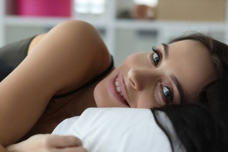 Portrait beautiful smiling female in pyjamas lying in bedroom. Pretty attractive brunette looking at camera with gladness and tenderness. Resting and relaxation concept