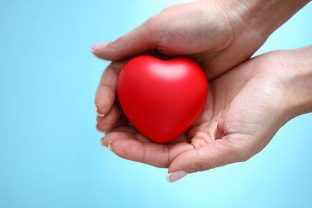 De vrouwenhand houdt rood stuk speelgoed hart ter beschikking tegen blauwe close-up als achtergrond. liefdadigheid mensen concept