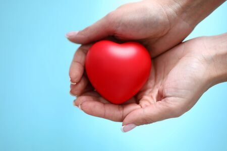 Main de femme tenir coeur de jouet rouge dans la main sur fond bleu agrandi. Concept de personnes caritatives