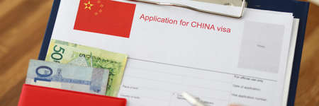 Male hand hold silver pen with passport. Filling China apllication form concept Stockfoto