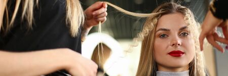 Beautiful Woman Getting Curly Hairstyle in Salon. Hairdresser Curling Hair for Young Female Client. Hairstylist Making Wavy Hairdo. Styling Curls for Girl with Red Lipstick Looking at Camera Shot