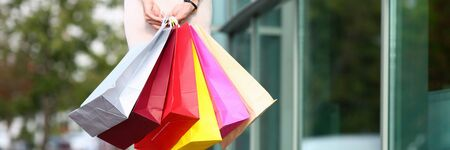 Focus on beautiful model in light clothes standing near fashionable boutique and holding multicolored shop packages. Fashion and shopping concept. Blurred background Stock Photo