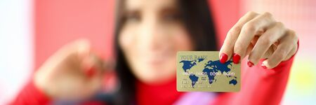 Focus on tender lady hand with red manicure of smart young woman showing golden bank master-card. Happy girl wearing fashionable outfit. Shopping concept. Blurred background