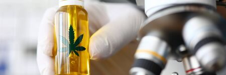 Focus on male hand in gloves holding glass bottle with cbd. Laboratory interior with microscope. Medicine and medical marijuana concept. Blurred background Foto de archivo