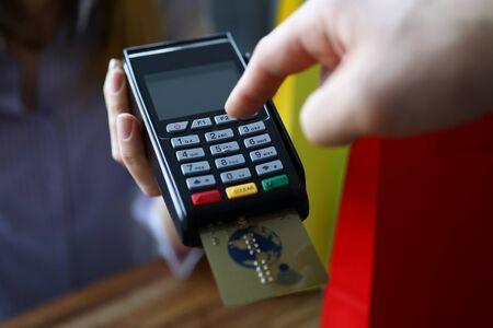 Pulsante maschio del contatore della mano sul terminale POS moderno sullo sfondo del negozio. Concetto di pagamento veloce.