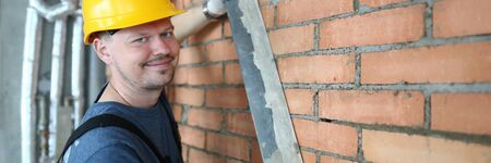 Portrait of constructor making brick wall smooth in order to plastering brick wall. Smiling construction master wearing protective outfit to prevent any trauma. Building concept