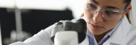 Adult caucasian beauty woman chemist in protective glasses looking at microscope against chemistry lab background. Medical analysis processing concept