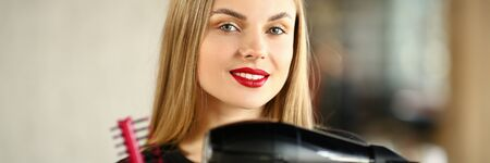 Girl Hairdresser Crossed Hands with Comb and Dryer. Beautiful Hairstylist Holding Hairbrush and Hairdryer for Styling Haircut. Blonde Stylist with Tool for Making Hairdo Looking at Camera Shot Banco de Imagens