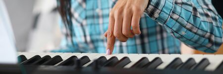 Focus on female hand playing synthesizer in music studio. Professional cute pianist learning new musical composition. Art and music concept. Blurred background Imagens
