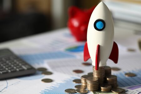 Close-up of rocket on pile of golden coins symbolizing company profits growth. Money scattered all around important charts and graphs. Start up and development concept