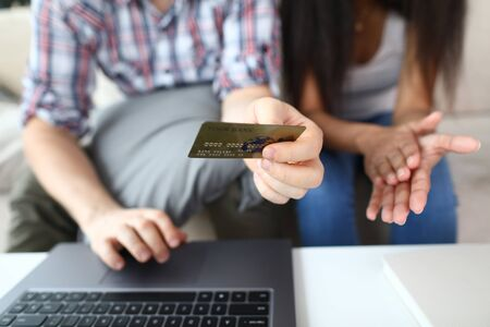Close-up of males hand holding credit card. Man and woman shopping online, buying tickets using plastic bankcard. Modern technology and e-payments concept