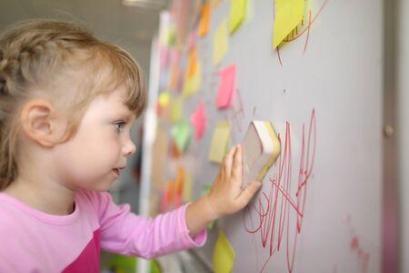 Vue rapprochée de l'enfant lave le tableau en classe avec une éponge. Enfant essuyant doodle écrit sur tableau noir. De nombreuses notes autocollantes sur tableau blanc. Notion d'enfance