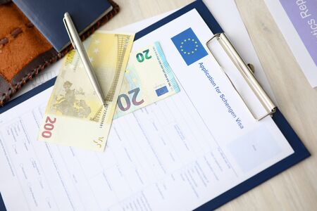 Close-up of clipboard with application for schengen visa document. Passport and paper banknotes on table. Form for personal information. European union and travelling abroad concept Zdjęcie Seryjne