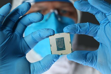 Cropped photo of engineer in protective mask and glasses showing microchip. Technology concept