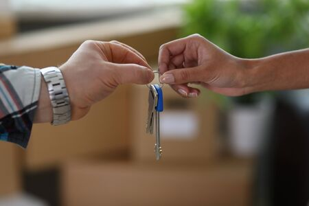 Close-up of male and female hands with keys from new house. Couple holding keychain. Purchase apartment, relocation and changing of living place concept