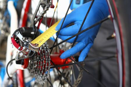 Close-up of male hands using measure tape for problem identification. Skilled mechanic working in bicycle repair shop service. Technical expertise concept