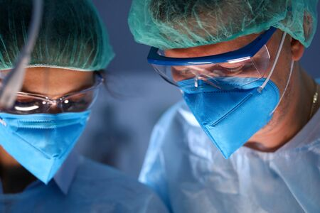 Close-up of serious professional surgeons in blue masks at operating room. Physician in medical glasses assisting during process. Medicine and healthcare concept Stok Fotoğraf