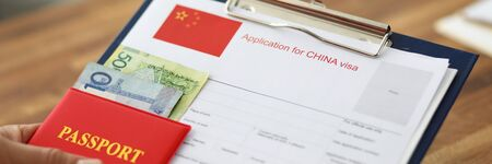 Male hand hold silver pen with passport. Filling China apllication form concept Zdjęcie Seryjne