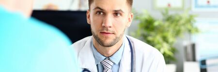 Portrait of worried physician talking and looking at colleague with fear and disturbance. Concerned man wearing stethoscope and white robe with striped tie. Medical treatment concept
