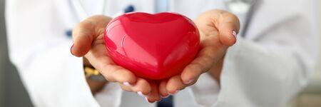 Weiblicher Kardiologe, der in der roten Spielzeugherznahaufnahme der Arme hält. Infarktschutz und Krankheitsprophylaxe langes und gesundes Lebenskonzept