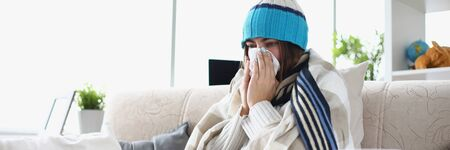 Portrait of woman having severe flu at home indoors and sneezing into tissue. Girl sitting in living room covered in blanket and suffering from common and annoying cold. Hard virus concept