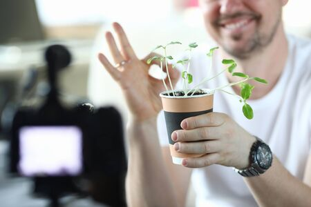 Male video blogger hold pot with green sprouts closeup background. Using camera and make selfie movie cincept