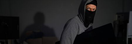 Portrait of male thug standing in dark room and holding expensive televisor from popular company. Man wearing grey hoodie and black mask. Stealth robbery concept