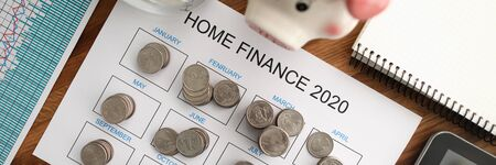 Top view of coin tover with paper calendar against wooden table background. Home finance 2020 concept