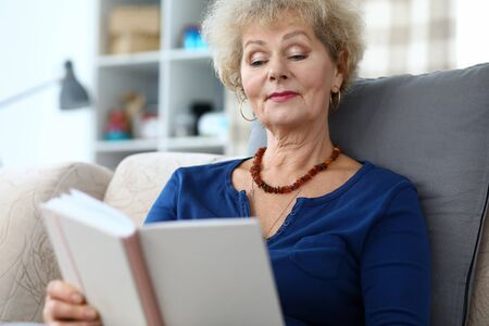 Portrait of adult woman reading interesting book. Aged curly-haired grandmother sitting on sofa at home. Smiling older grandma enjoying free time. Retirement vacation concept