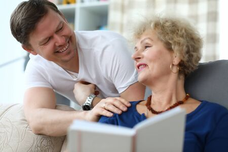 Portrait of happy cheerful relatives smiling at home. Smiling adult man having fun with aged mom. Cheerful woman enjoying reading book at home. Friendly family concept