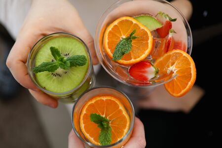 Top view of three different delicious cocktails with mint and juicy fruits. People holding cold fresh beverages in glasses. Festive celebration and holiday concept