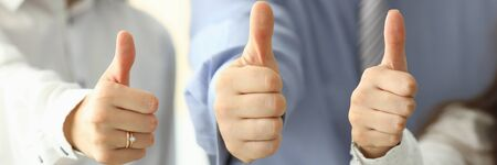 Focus on tender female and male hands showing big thumb up and posing at modern workplace. Businesspeople working in office together. Teamwork concept