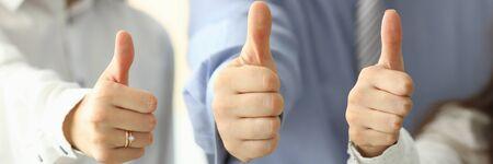 Focus op tedere vrouwelijke en mannelijke handen met grote duim omhoog en poseren op moderne werkplek. Ondernemers werken samen op kantoor. Teamwerk concept