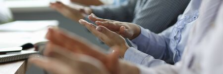 Close-up of business people hands. Man and woman sitting in office conference room and applauding on biz presentation of new project. Teamwork concept