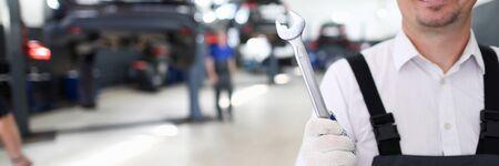 Portret wesoły mężczyzna trzymając lśniący klucz metalowy i stojący w nowoczesnym garażu samochodowym z wieloma samochodami. Koncepcja naprawy maszyn i stacji obsługi
