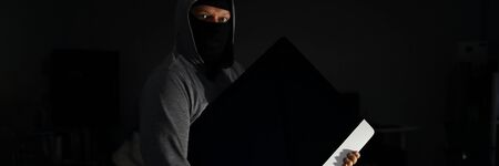 Portrait of terrified thug holding electronics of popular company in hands. Criminal wearing black mask and grey hoodie in order to cover identity. Stealth robbery concept Stok Fotoğraf