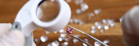 Goldsith in white gloves hold tweezers with pink gemstone and magnifier lens closeup background. Assessment of quality diamonds concept