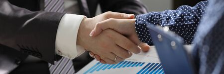 Businessman and woman hand shake indoor office teambuilding background closeup. Equality business education concept