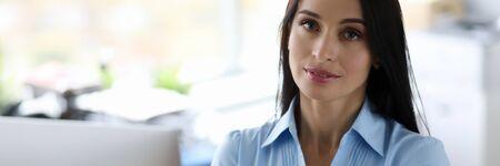 Millennial businesswomen in blue shirt armcrossed office portrait. Business education concept