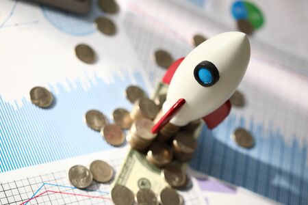 Investment profitability planning and analysis. Model space rocket stands on table next to coins. Calculation attractiveness financial project. Profitability analysis and startup promotion.