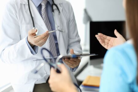 Meeting doctors and discussion patient's illness. Male doctor in white coat with stethoscope on his neck holds data folder and discusses working issues with female doctor, view from back.
