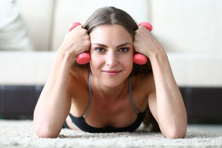 Girl learns to correctly perform exercises at home. Exercises with dumbbells give good load on all muscles. Beginner training with small weight. Girl resting lying on floor and holds dumbbells Reklamní fotografie