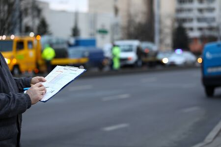 Filling out accident statement at scene accident. Man fills document standing on road. Driver draws up general statement accident, signs it. Claim settlement document. Document for insurance company. Standard-Bild