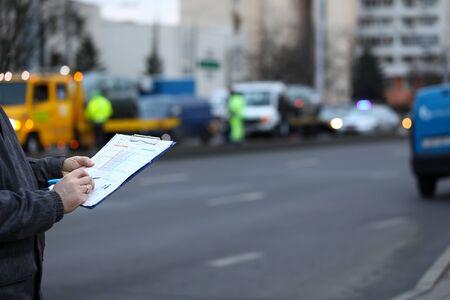 Llenando la declaración del accidente en la escena del accidente. El hombre llena el documento que está parado en la carretera. Conductor redacta accidente de declaración general, lo firma. Documento de liquidación de reclamaciones. Documento para compañía de seguros. Foto de archivo
