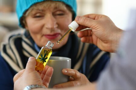Elderly woman receives sedative drops from doctor. Close up an elderly woman looking at cup. Doctor collected carly hemp oil and drips them into patient cup. Prescription herbal drops. 写真素材