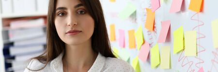 Portrait of smart designer standing in modern office and looking at camera with gladness. Pretty woman working near big wall with colorful stickers. Blurred background